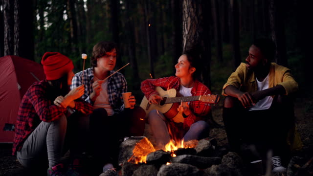 Happy-men-and-women-are-sitting-around-fire-cooking-marshmallow-playing-the-guitar-and-singing-during-hike-in-forest-Young-people-are-having-fun-and-enjoying-nature-