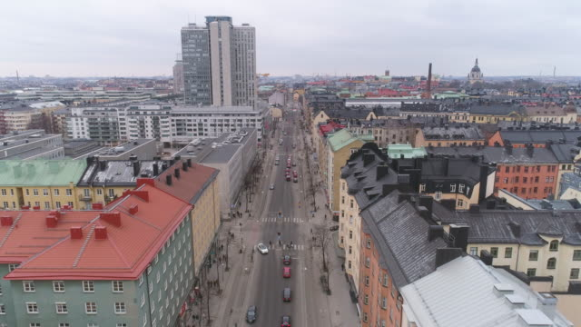 Stockholm-city-street-aerial-view-Drone-shot-flying-over-street-and-buildings-in-Södermalm-district-Cityscape-skyline-in-The-Capital-of-Sweden-Skrapan-skyscraper-building-in-the-background