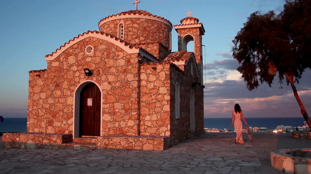 Hermosa-mujer-griega-a-cerca-de-la-antigua-iglesia-con-vista-al-espectacular