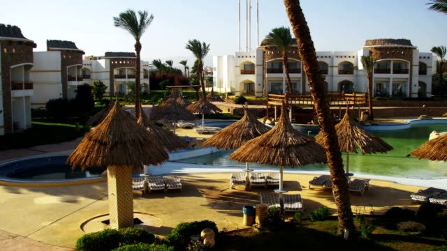 Sunny-Hotel-Resort-with-Blue-Pool-Palm-Trees-and-Sunbeds-in-Egypt
