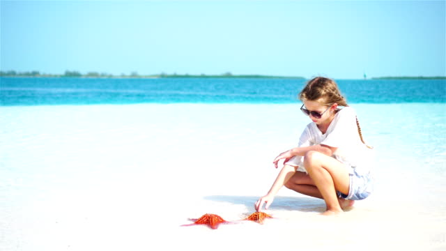 Adorable-little-girl-holding-giant-red-starfish-on-white-empty-beach