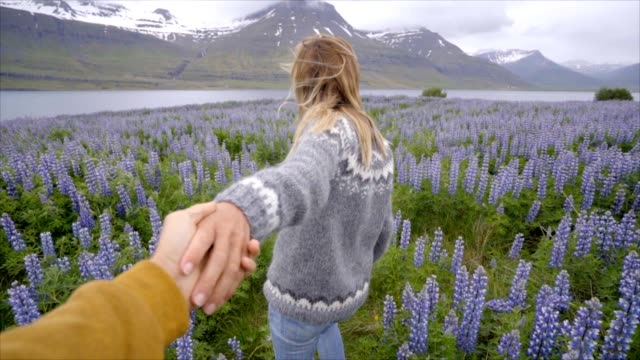 Follow-me-to-Iceland-girlfriend-leading-man-to-flower-lupine-field-near-lake-and-mountains-People-travel-concept--4K-video