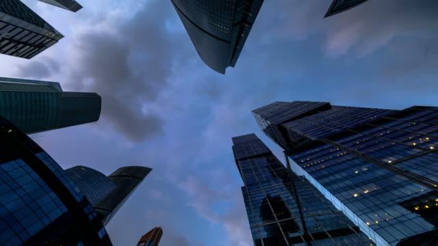 Bottom-up-Blick-auf-rotierende-Wolkenkratzer-und-fliegenden-Wolken-Zeitraffer-hyper-Zeitraffer
