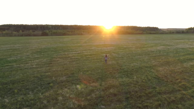 Unrecognizable-woman-walking-on-the-field-at-sunset-arms-outstretched-