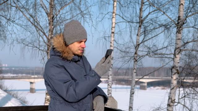 Hombre-en-azul-por-la-chaqueta-con-capucha-de-piel-utilizando-teléfono-móvil-para-video-chat-y-sonrientes-en-el-parque-de-invierno-