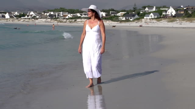 Woman-walking-along-the-water-line-on-the-beach-Cape-Town-South-Africa