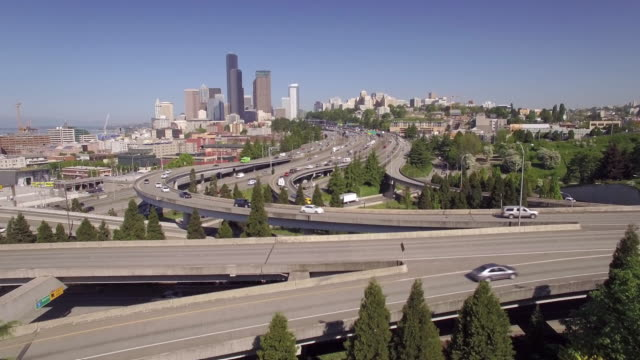 Slow-Aerial-Fly-Over-Downtown-Seattle-Freeway-to-Reveal-Skyscraper-Buildings-in-Skyline-on-Sunny-Day