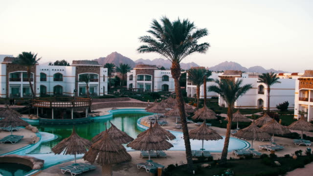 Hotel-Resort-with-Blue-Pool-Palm-Trees-and-Sunbeds-in-Egypt
