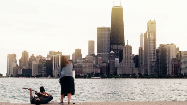 Young-creative-couple-on-the-shore-of-Michigan-lake-Chicago-America-Woman-draw-ma-play-guitar-lying-on-shore