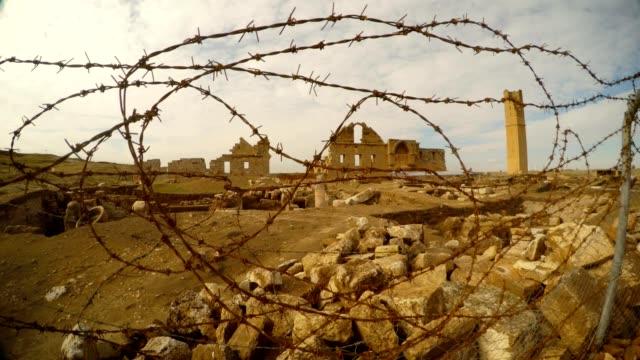 hinter-dem-Stacheldraht-Draht-die-Ruinen-der-Muslim-University-an-der-Grenze-zwischen-der-Türkei-und-Syrien