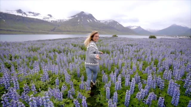 Sígueme-a-Islandia-novia-agitando-la-mano-en-el-hombre-al-campo-altramuz-de-flor-cerca-del-lago-y-las-montañas-personas-viajan-concepto---4K-video