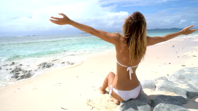 Una-joven-mujer-sentada-en-la-playa-de-arena-blanca-en-la-isla-tropical-de-Filipinas