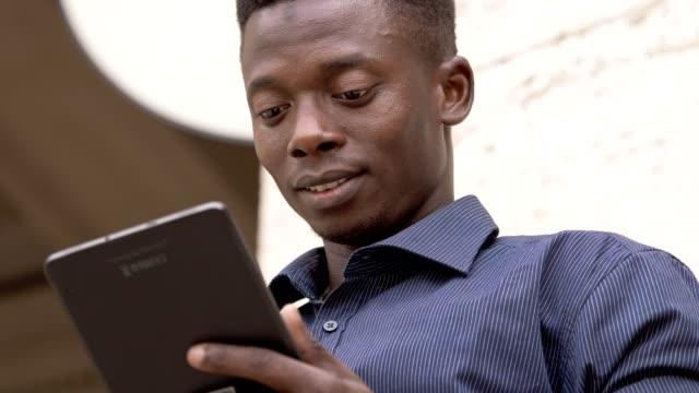 Relajado-negro-africano-hombre-de-la-calle-con-tableta-digital