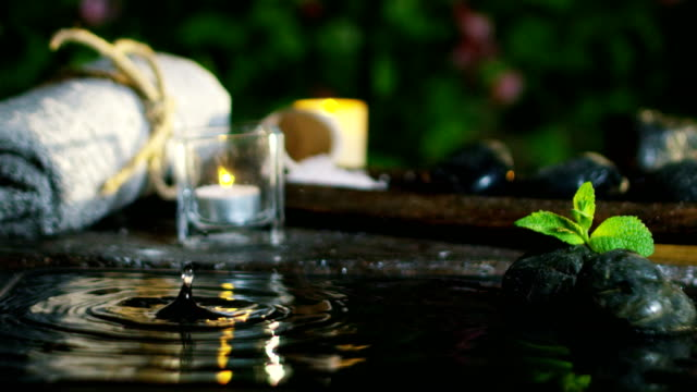 Dispara-a-agua-hermosa-y-la-composición-de-spa-y-wellness-de-velas-en-extremo-lento-motion-concept-de-relax-y-meditation-water