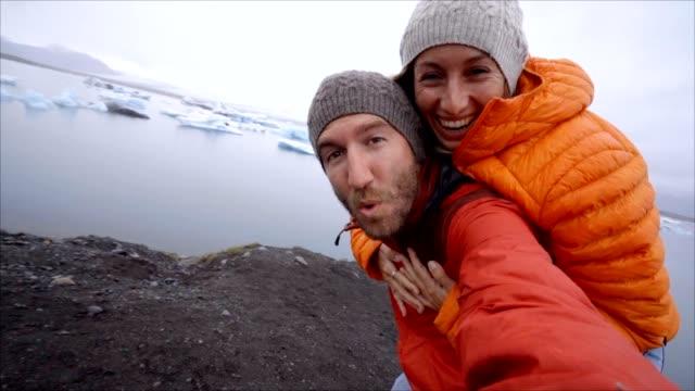 Video-de-pareja-de-jóvenes-que-se-divierten-tomando-selfie-en-el-lago-de-glaciar-en-la-laguna-Jokulsarlon-en-Islandia-