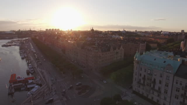 Aerial-view-of-Stockholm-cityscape-at-sunset-Drone-shot-flying-over-buildings-street-and-canal-Capital-city-of-Sweden