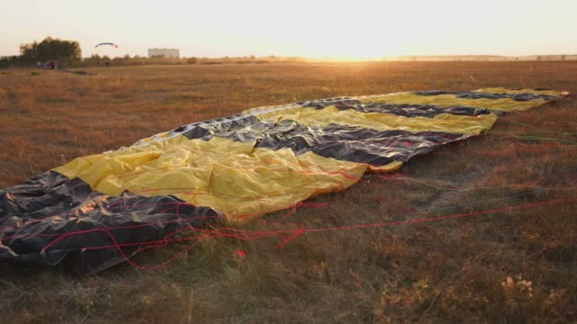 Parachute-lying-on-the-ground-in-the-sunset-rays-of-the-sun-on-the-airfield