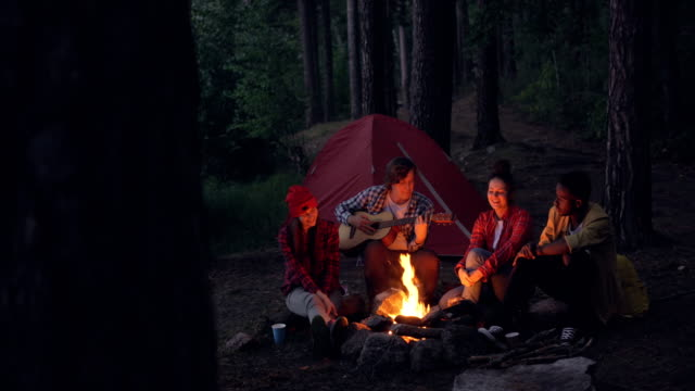 Multiracial-group-of-friends-hikers-is-playing-the-guitar-singing-and-laughing-around-campfire-in-the-evening-Summertime-fun-nature-and-leisure-concept-