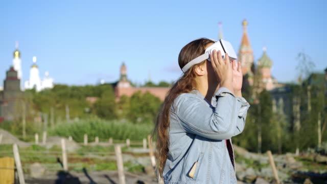 Mujer-joven-en-gafas-VR-en-el-fondo-de-la-ciudad