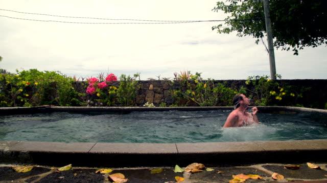 man-jumping-in-pool-and-splashing-water