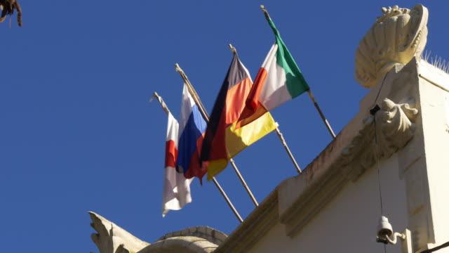 Día-soleado-banderas-europeas-meciéndose-al-viento-en-el-último-piso-4-k-barcelona-España