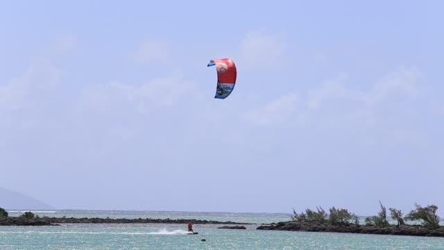 Man-kitesurfing-in-ocean-extreme-summer-sport-in-island-Mauritius