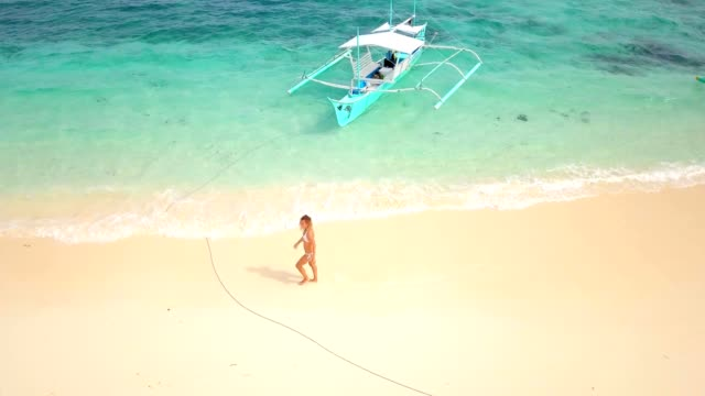 Drone-shot-aerial-view-of-young-woman-walking-on-idyllic-tropical-beach