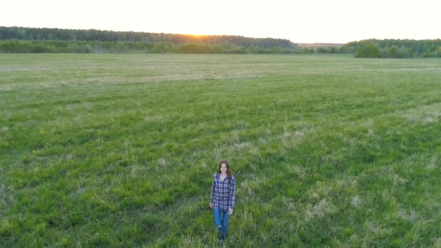 Woman-walking-on-the-field-at-sunset-