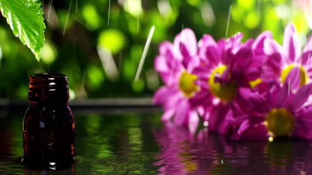 Mischung-aus-ätherischen-Ölen-mit-Wassertropfen-Düfte-und-Aromen-in-der-Aromatherapie-für-Wellness-und-Spa-Konzept-der-Schönheit-Duftende-ätherische-Öl-Essenz-Tropfen-fallen-von-einem-Blatt-in-Pool-im-Wellness-center