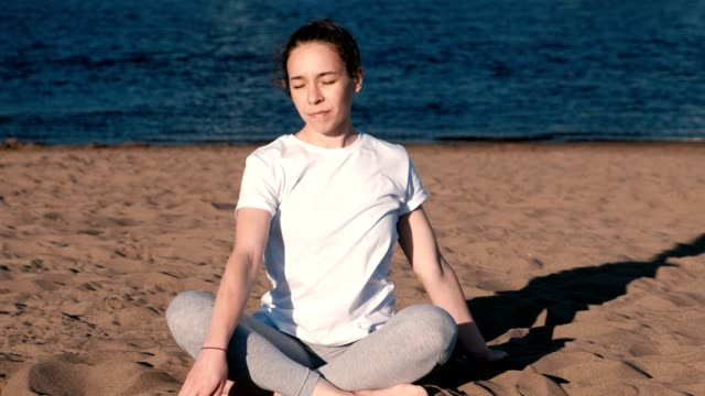 Mujer-de-estiramientos-yoga-en-la-playa-por-el-río-en-la-ciudad-Hermosa-vista-Incline-la-cabeza-hacia-el-lado-