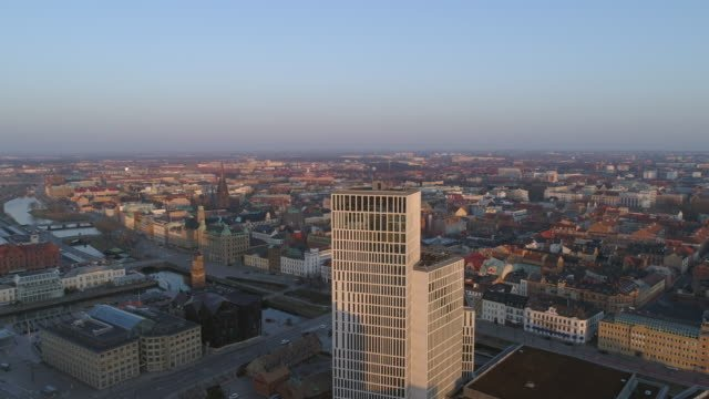 Drone-shot-flying-down-by-modern-skyscraper-office-buildings-in-Malmö-city-Sweden-Aerial-view-of-Malmoe-cityscape-skyline-at-sunset