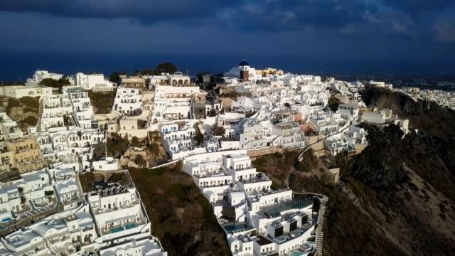 Sobrevuelo-de-pueblo-de-Imerovigli-y-roca-Skaros-en-puesta-del-sol-isla-de-Santorini-Grecia