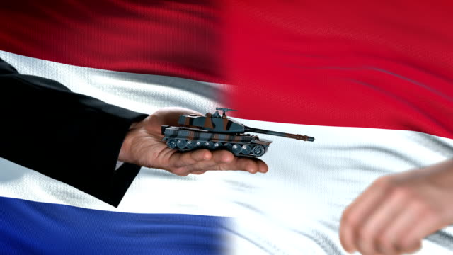 Netherlands-and-Indonesia-officials-exchanging-tank-for-money-flag-background