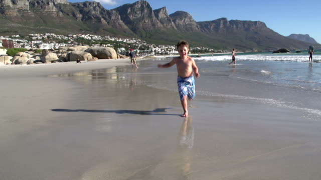 Young-boy-running-towards-the-camera-along-the-beach-South-Africa
