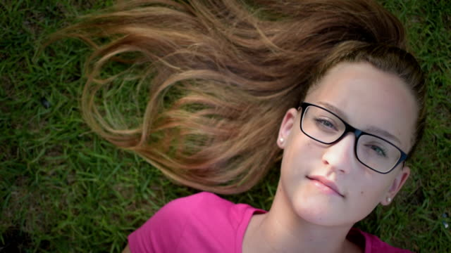 Cheerful-teenage-girl-lying-on-the-grass-and-looking-at-the-sky-shoot-from-above
