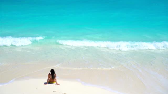 Mujer-joven-en-la-playa-de-vista-de-aguas-arriba