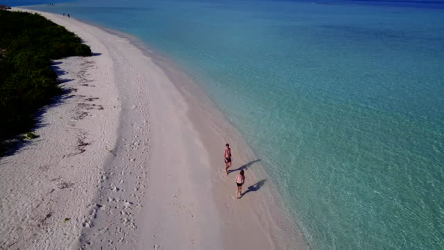 v03813-Aerial-flying-drone-view-of-Maldives-white-sandy-beach-on-sunny-tropical-paradise-island-with-aqua-blue-sky-sea-water-ocean-4k-2-people-young-couple-man-woman-playing-ball-fun-together