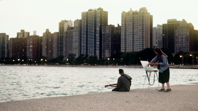 Young-Beautiful-couple-on-the-shore-of-Michigan-lake-Chicago-America-Woman-draw-man-play-guitar