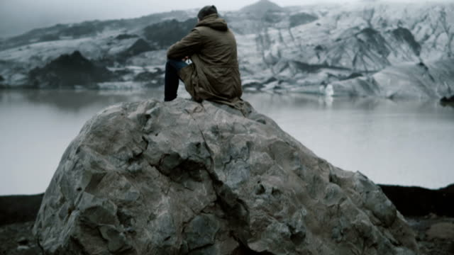 Back-view-of-young-man-sitting-on-the-volcanic-rock-alone-and-looking-on-the-glaciers-in-Ice-lagoon-in-Iceland