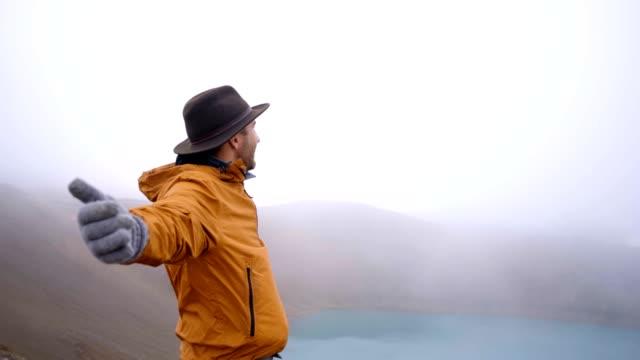 Hombre-joven-de-brazos-extendidos-en-el-espectacular-lago-de-cráter-en-Islandia