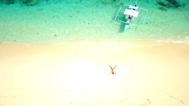 Drone-shot-aerial-view-of-young-woman-lying-down-like-star-shape-on-idyllic-tropical-beach-shot-in-the-Philippines