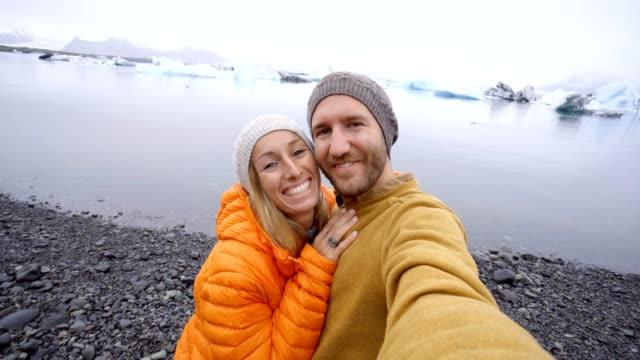 4-K-Video-de-pareja-de-jóvenes-que-se-divierten-tomando-selfie-en-el-lago-de-glaciar-en-la-laguna-Jokulsarlon-en-Islandia-Dos-personas-viajan-romance-amor-compartir-el-concepto-de-comunicación-de-estar-juntos-Primavera-las-temperaturas-frías