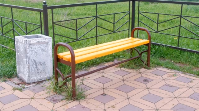 Bench-by-the-fence-in-park-Near-the-trash-