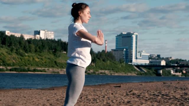 Mujer-de-estiramientos-yoga-en-la-playa-por-el-río-en-la-ciudad-Vista-hermosa-ciudad-