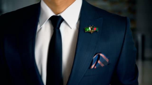 Empresario-caminando-hacia-cámara-con-amigo-país-banderas-Pin-Pakistán---Bangladesh