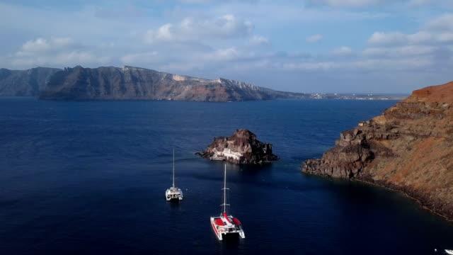 Vuelo-sobre-Iglesia-de-la-pequeña-isla-(Nisis-Agios-Nikolaos)-cerca-de-la-ciudad-de-Oia-isla-de-Santorini-Grecia