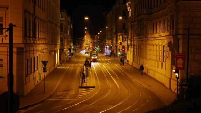 Plaza-de-Silingrovo-en-Brno-pasando-por-el-transporte-público-durante-la-noche-larga-calle-de-la-parada-de-tranvía-de-timelapse