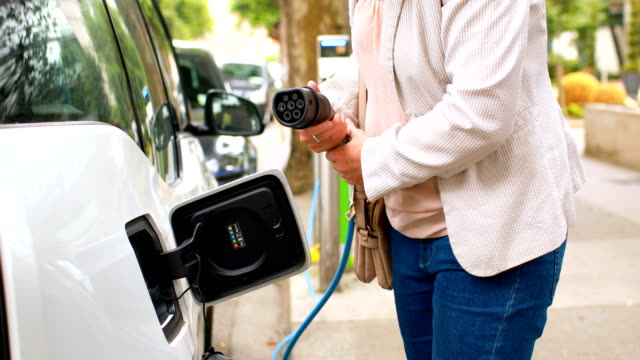 Mujer-que-carga-un-coche-eléctrico-en-estación-4k-de-carga