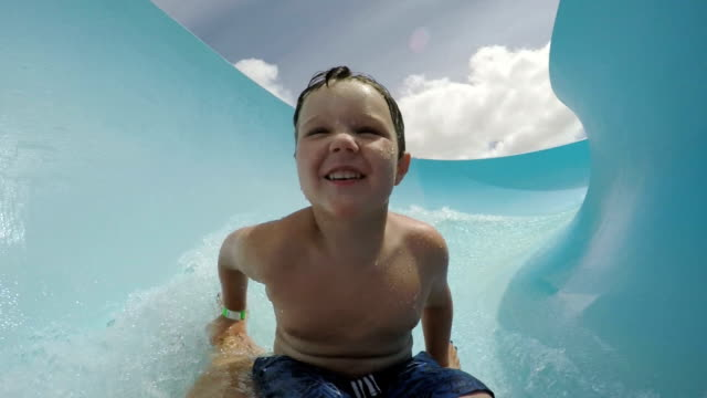 Happy-young-boy-going-down-curved-waterslide-in-slow-motion