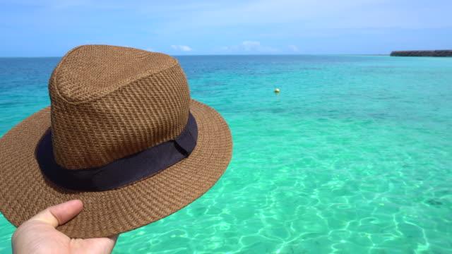 Mano-que-sostiene-el-sombrero-Panamá-de-vacaciones-con-vistas-al-paraíso